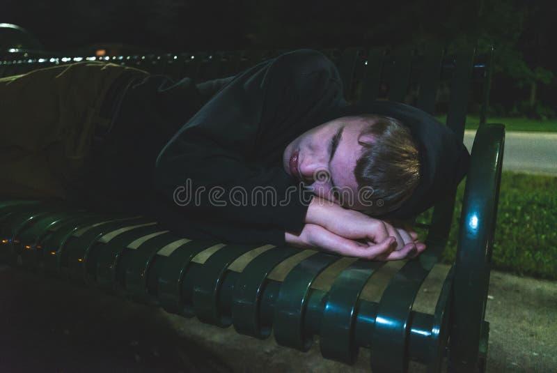 Adolescente sin hogar que duerme en un banco de parque imágenes de archivo libres de regalías