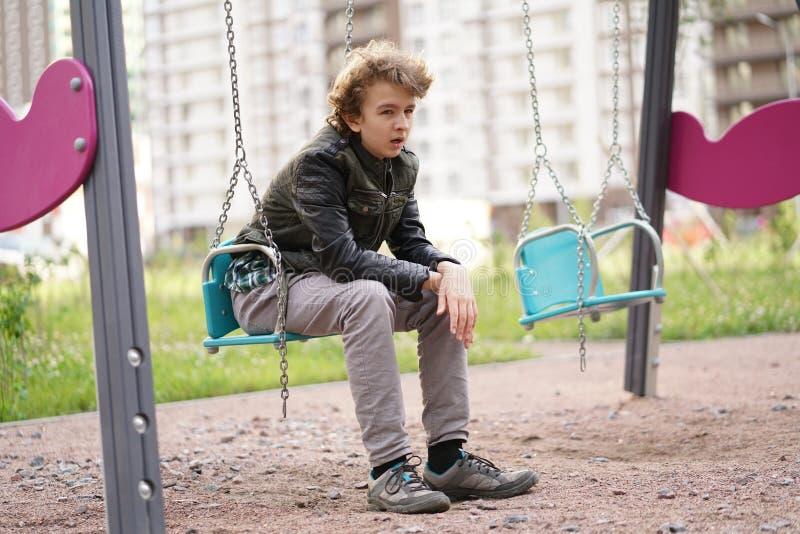 Adolescente solo triste al aire libre en el patio las dificultades de la adolescencia en concepto de la comunicaci?n imagen de archivo