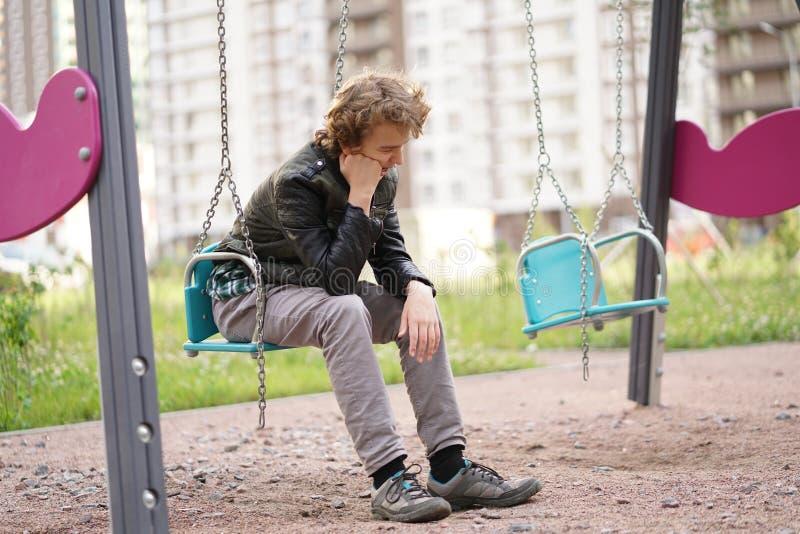 Adolescente solo triste al aire libre en el patio las dificultades de la adolescencia en concepto de la comunicaci?n fotos de archivo