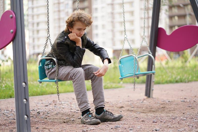Adolescente solo triste al aire libre en el patio las dificultades de la adolescencia en concepto de la comunicaci?n foto de archivo libre de regalías
