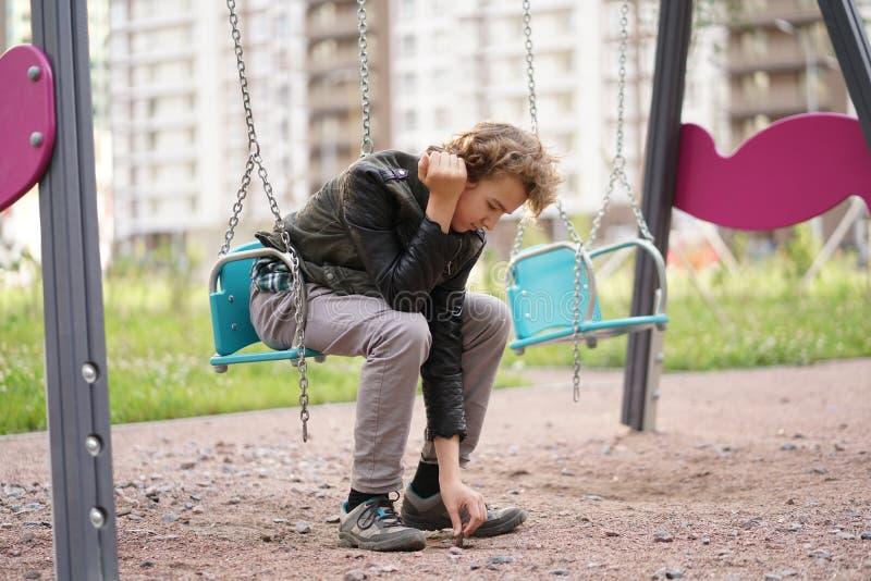 Adolescente solo triste al aire libre en el patio las dificultades de la adolescencia en concepto de la comunicaci?n fotografía de archivo libre de regalías