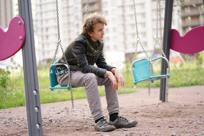 Adolescente solo triste al aire libre en el patio las dificultades de la adolescencia en concepto de la comunicaci?n foto de archivo