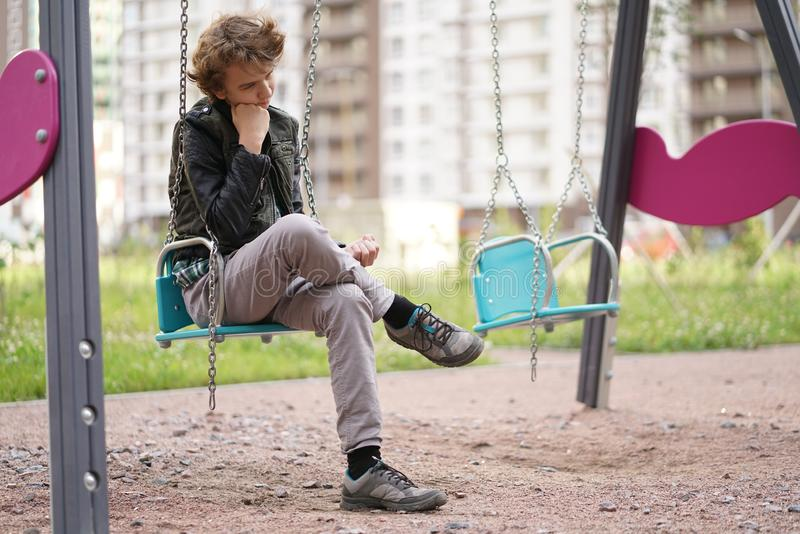 Adolescente solo triste al aire libre en el patio las dificultades de la adolescencia en concepto de la comunicaci?n imagen de archivo libre de regalías
