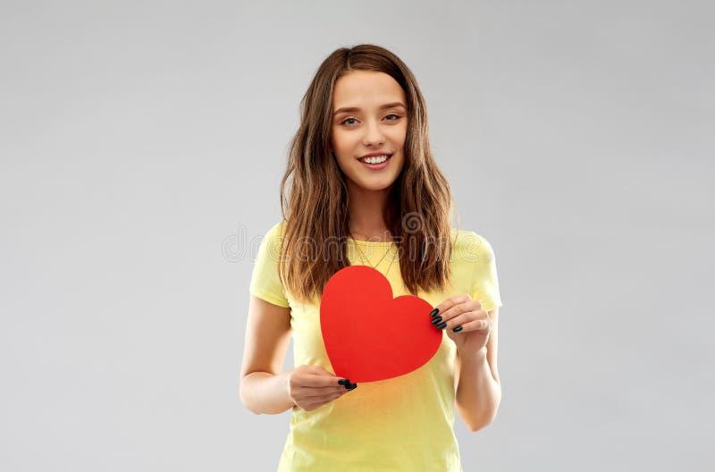 Adolescente sonriente con el coraz?n rojo fotos de archivo