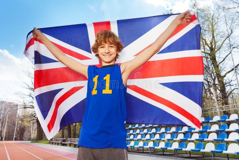 Adolescente sonriente con la bandera británica en un estadio imagenes de archivo