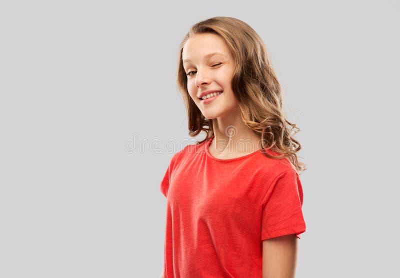 Adolescente sonriente en el guiño rojo de la camiseta imagenes de archivo