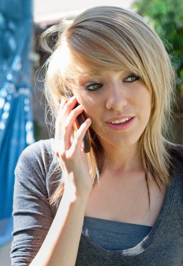 Adolescente sonriente en el teléfono móvil imágenes de archivo libres de regalías