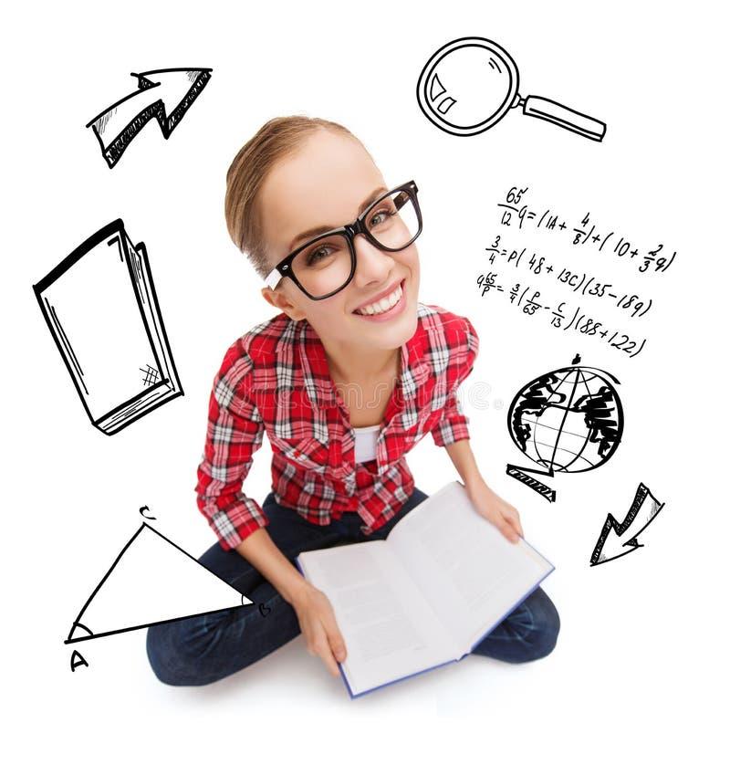 Adolescente sonriente en libro de lectura de las lentes fotografía de archivo libre de regalías