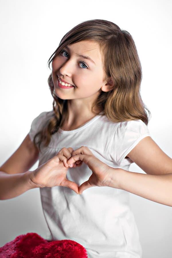 La muchacha muestra el corazón de los dedos fotos de archivo