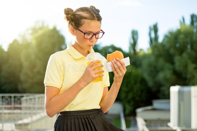 Adolescente sonriente lindo de la colegiala que sostiene una hamburguesa y un zumo de naranja imagen de archivo libre de regalías