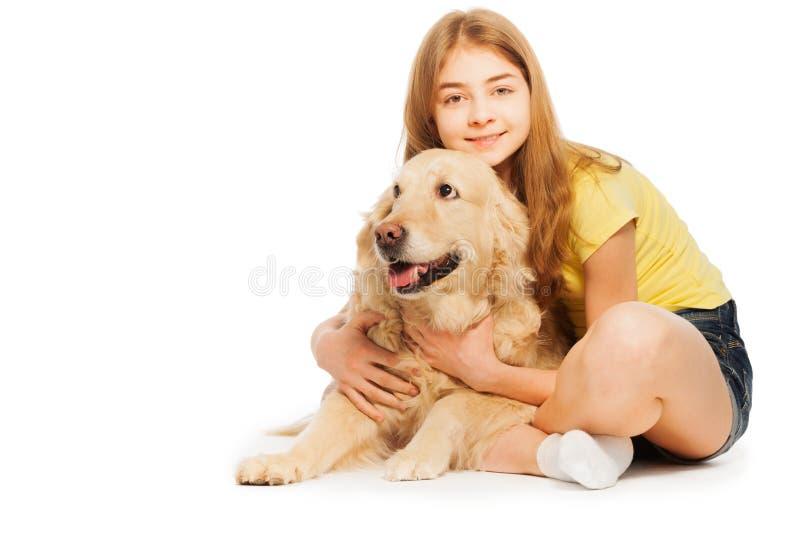 Adolescente sonriente que se sienta con golden retriever foto de archivo libre de regalías