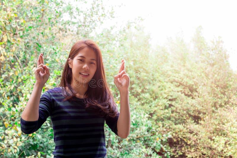 Adolescente sonriente que sostiene los fingeres cruzados para la buena suerte sobre fondo de la naturaleza imágenes de archivo libres de regalías