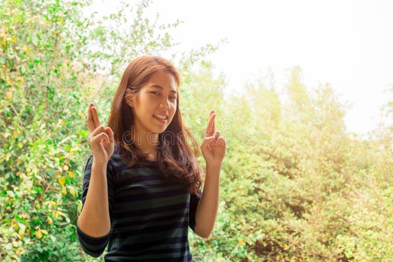 Adolescente sonriente que sostiene los fingeres cruzados para la buena suerte sobre fondo de la naturaleza imagenes de archivo