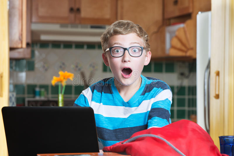 Adolescente sorprendida con el ordenador portátil y el bookbag en cocina fotos de archivo