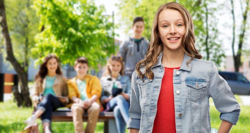 Adolescente sorridente in rivestimento del denim sopra gli amici immagini stock libere da diritti