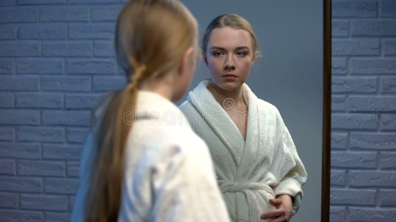 Adolescente spaventato che tiene pancia incinta che guarda in specchio, irresponsabilità fotografia stock