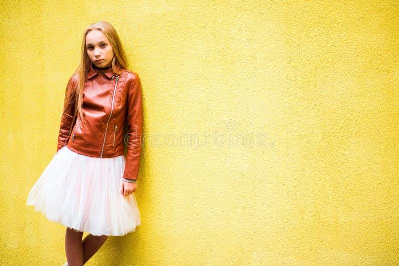 Adolescente su un fondo giallo della parete fotografie stock