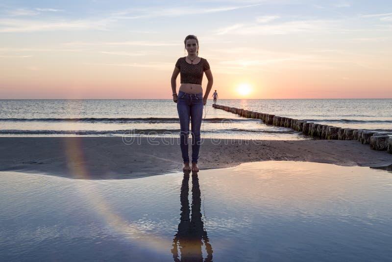 Adolescente sur la plage au coucher du soleil photos libres de droits