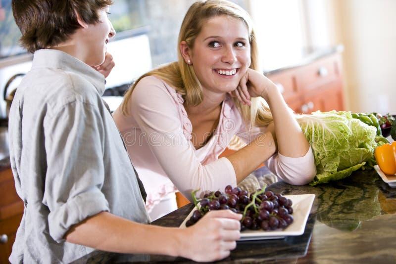 Adolescente sur le compteur de cuisine avec le frère photographie stock libre de droits