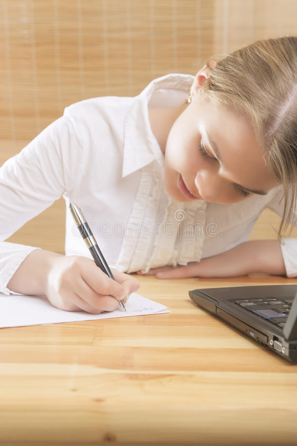 Adolescente sveglio che scrive al suo compito t la Tabella fotografia stock