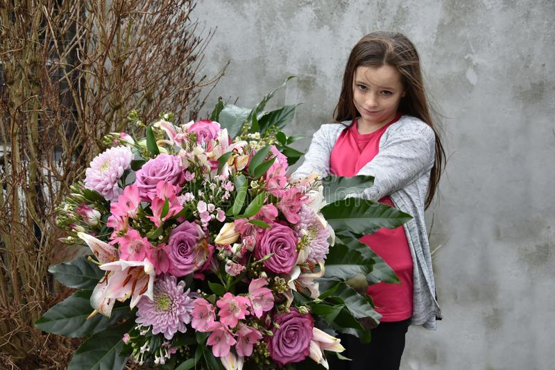 Adolescente tímido com grande grupo de flores fotos de stock