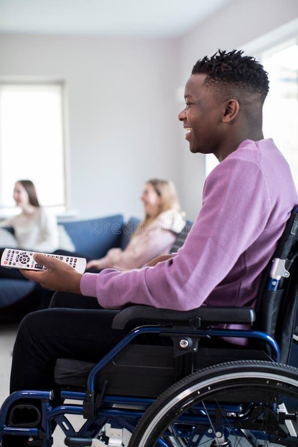 Adolescente in televisione di sorveglianza della sedia a rotelle con gli amici a casa fotografia stock libera da diritti