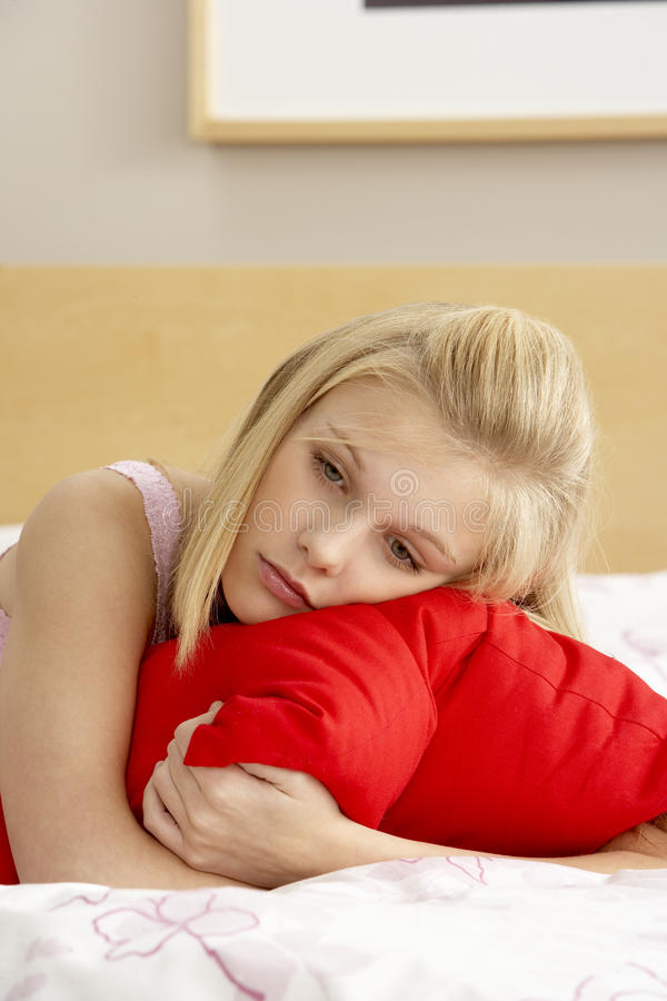 Adolescente triste in camera da letto che abbraccia cuscino fotografie stock libere da diritti