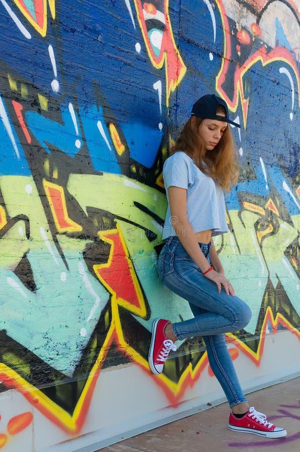 Adolescente triste che pende contro una parete dei graffiti fotografia stock libera da diritti