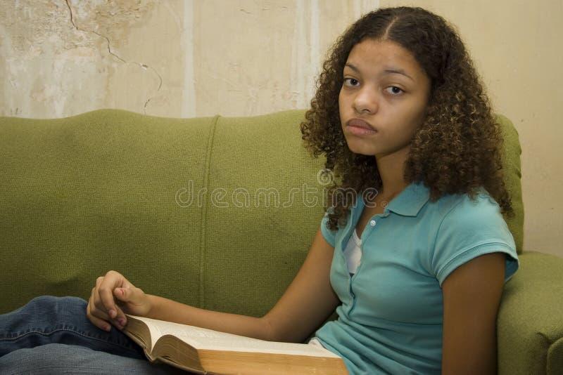 Adolescente triste com o livro no apartamento imagens de stock royalty free