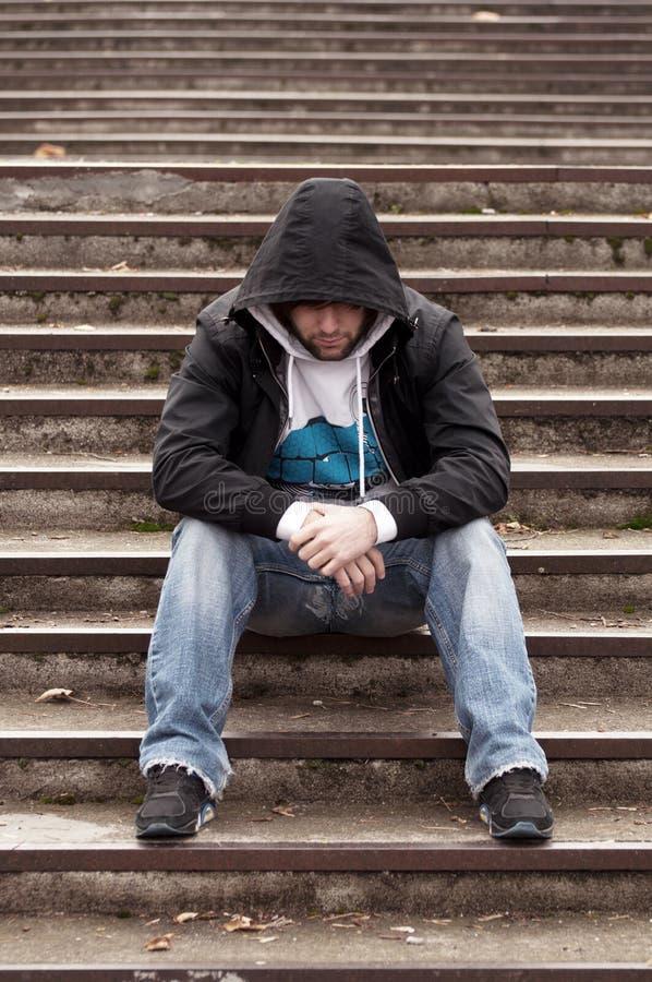 Adolescente triste con el capo motor que se sienta en las escaleras fotografía de archivo libre de regalías