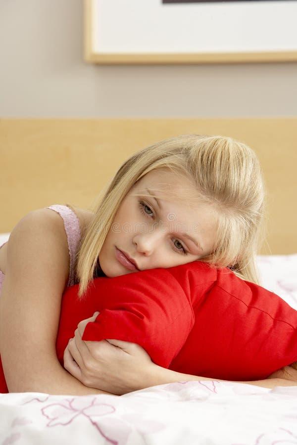 Adolescente triste dans la chambre à coucher étreignant l'oreiller photos libres de droits