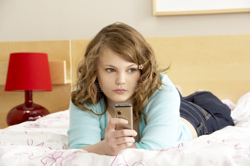 Adolescente triste dans la chambre à coucher avec le téléphone portable photo libre de droits