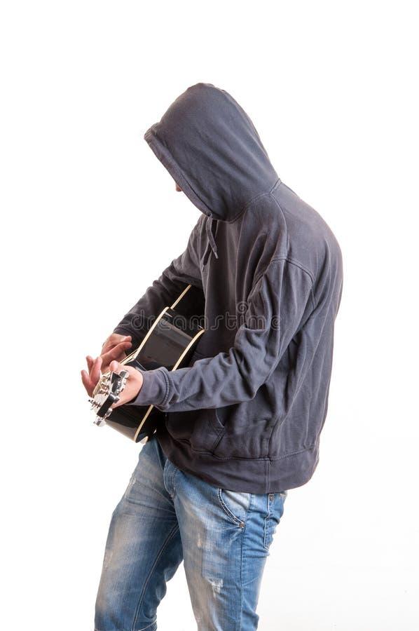 Adolescente triste en la sudadera con capucha negra que toca la guitarra acústica imagen de archivo