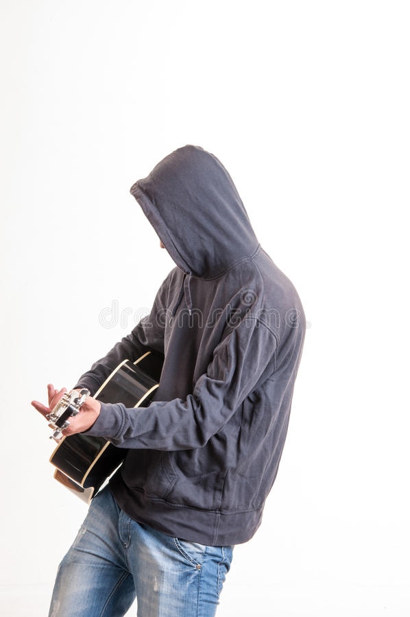 Adolescente triste en la sudadera con capucha negra que toca la guitarra acústica imágenes de archivo libres de regalías