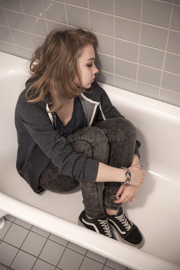 Adolescente triste forçado que senta-se no banho vazio imagens de stock