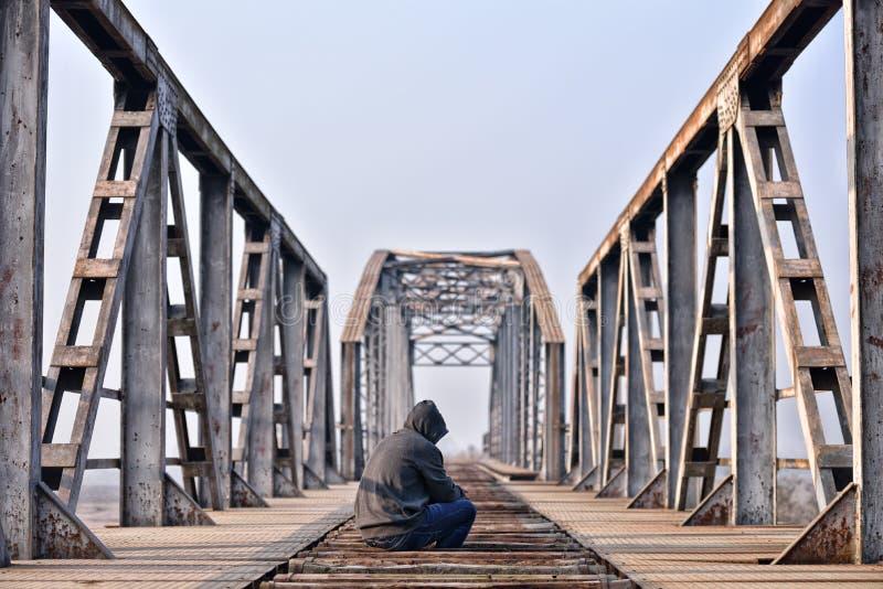 Adolescente triste nella depressione che si siede su un ponte al tramonto fotografie stock