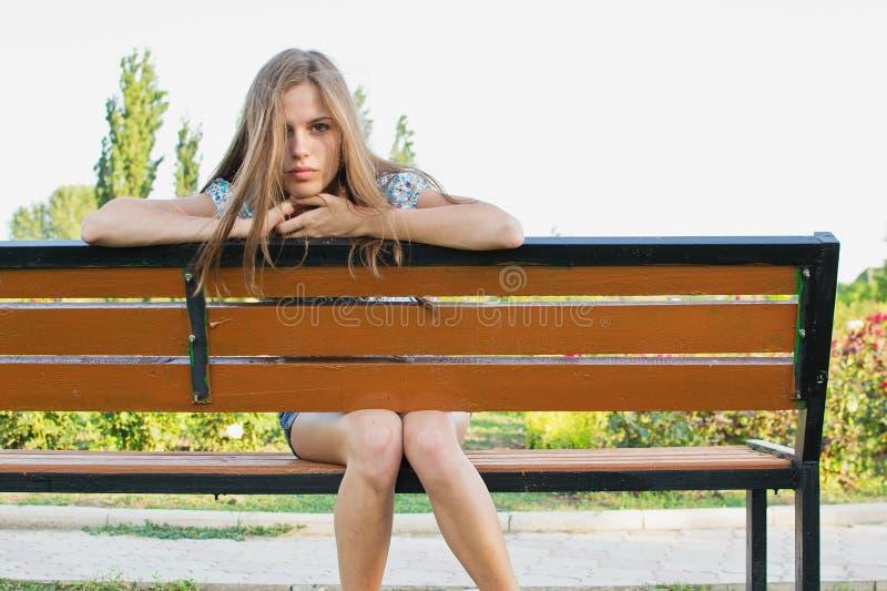 Adolescente triste no banco de parque imagem de stock royalty free