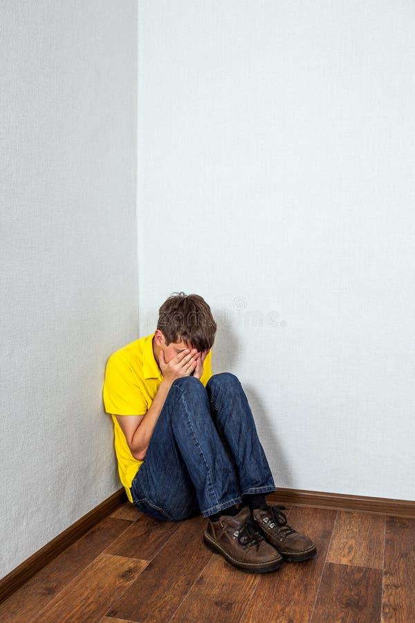 Adolescente triste no canto foto de stock