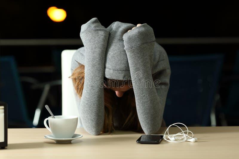 Adolescente triste que queixa-se em uma barra na noite imagem de stock
