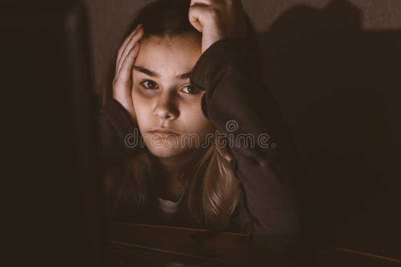 Adolescente triste que se sienta cerca del ordenador portátil en sitio oscuro foto de archivo