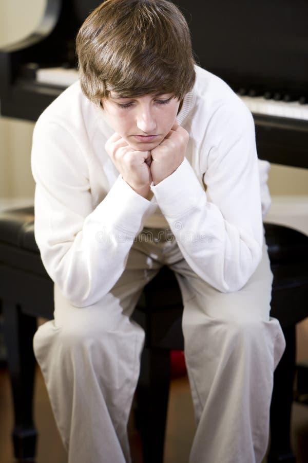 Adolescente triste que se sienta con la barbilla en las manos foto de archivo libre de regalías