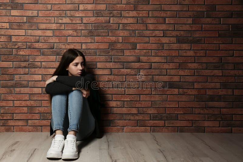 Adolescente turbato che si siede sul pavimento vicino alla parete fotografia stock libera da diritti