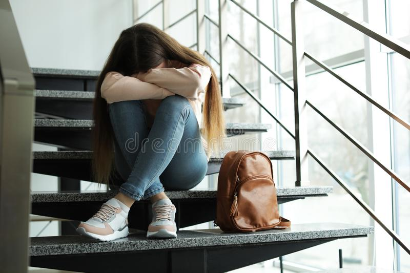 Adolescente turbato con lo zaino che si siede sulle scale fotografie stock libere da diritti