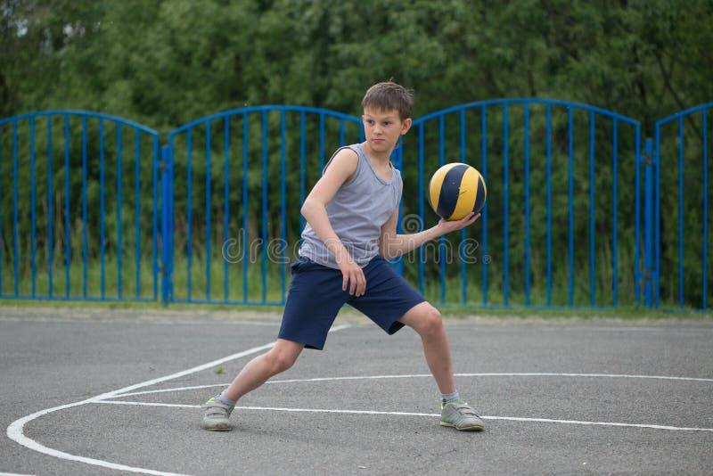 Adolescente in una maglietta e negli shorts che giocano con una palla immagine stock