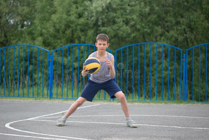 Adolescente in una maglietta e negli shorts che giocano con una palla fotografie stock