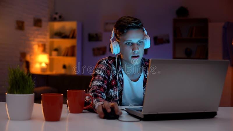 Adolescente viciado que joga jogos de computador no port?til, lote dos copos que est?o no lado fotos de stock