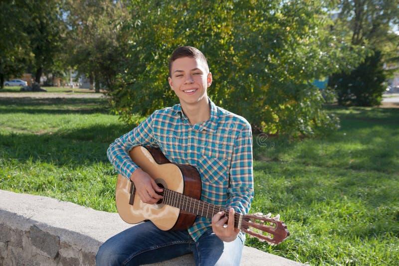 Adolescente y guitarra en primavera foto de archivo libre de regalías