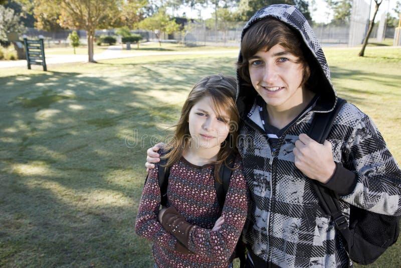 Adolescente y hermana joven con los morrales de la escuela imagen de archivo libre de regalías
