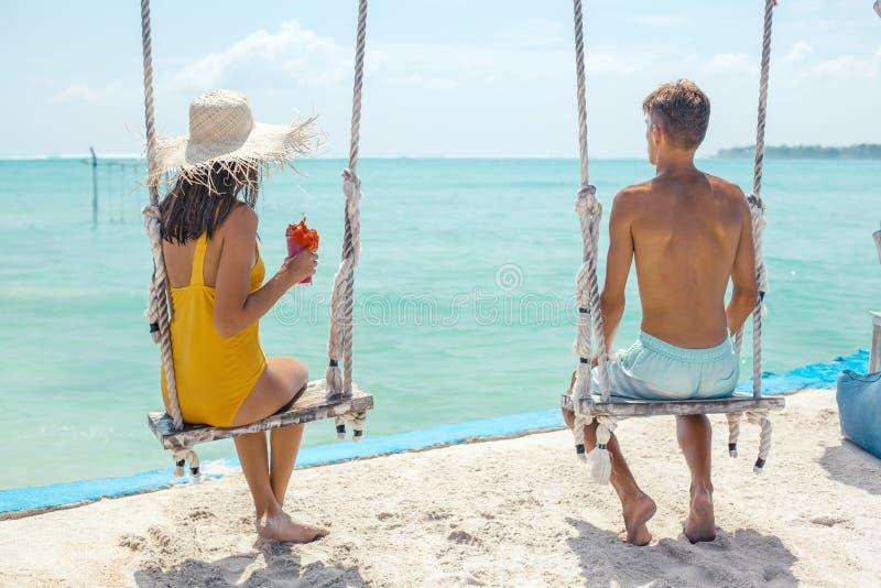 Adolescente y muchacho que cuelgan en oscilaciones con una opinión del mar en café de la playa fotos de archivo