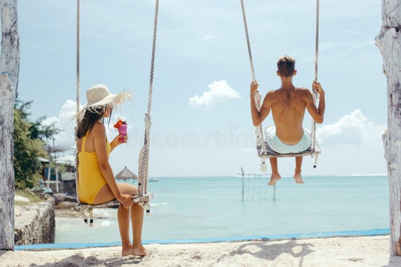 Adolescente y muchacho que cuelgan en oscilaciones con una opinión del mar en café de la playa imagenes de archivo